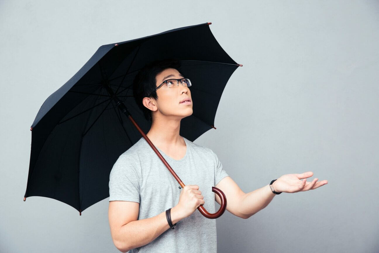 Asian man standing with umbrella