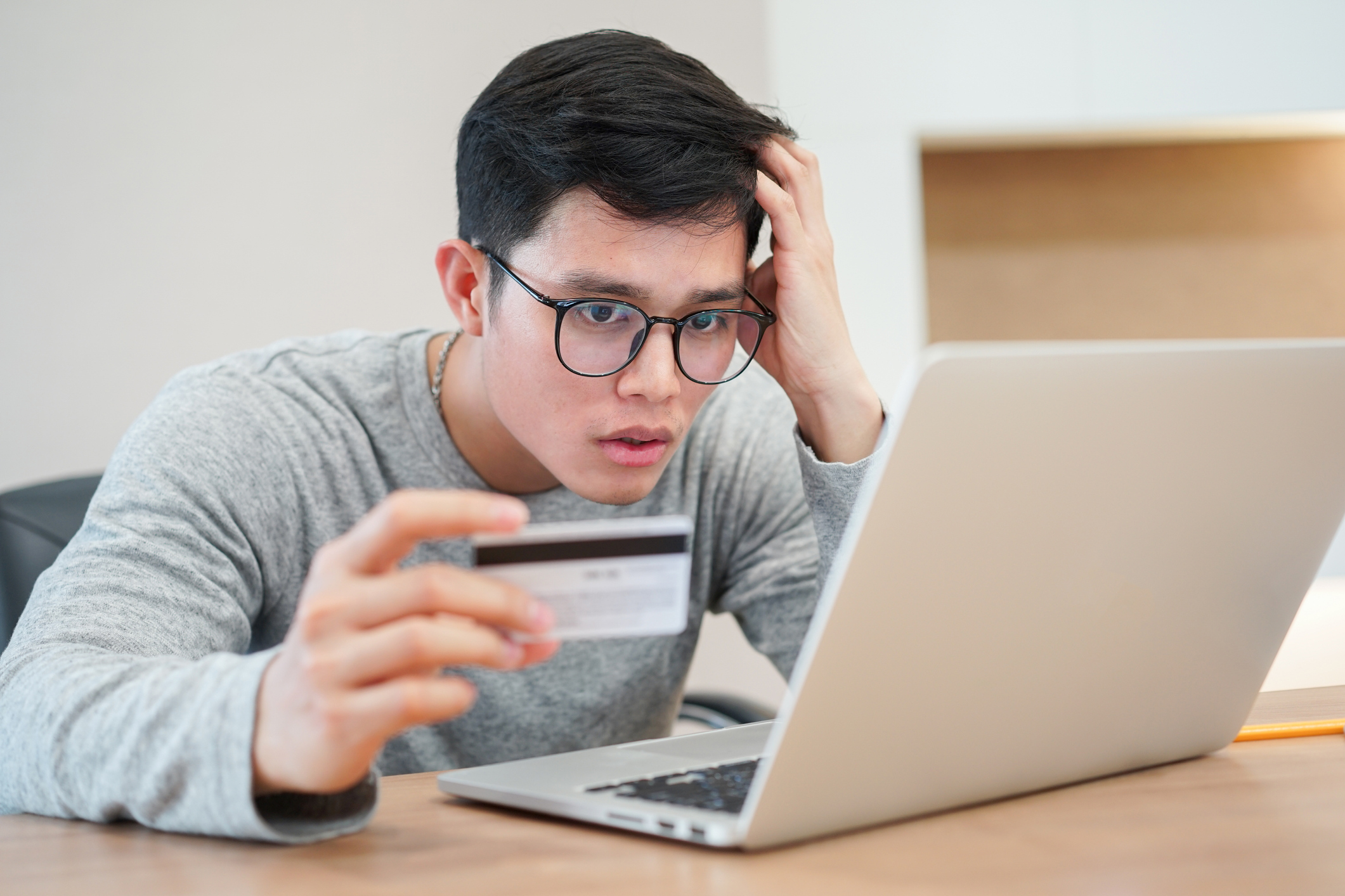 close up on young asian man feeling shock after make payment by credit card but website e