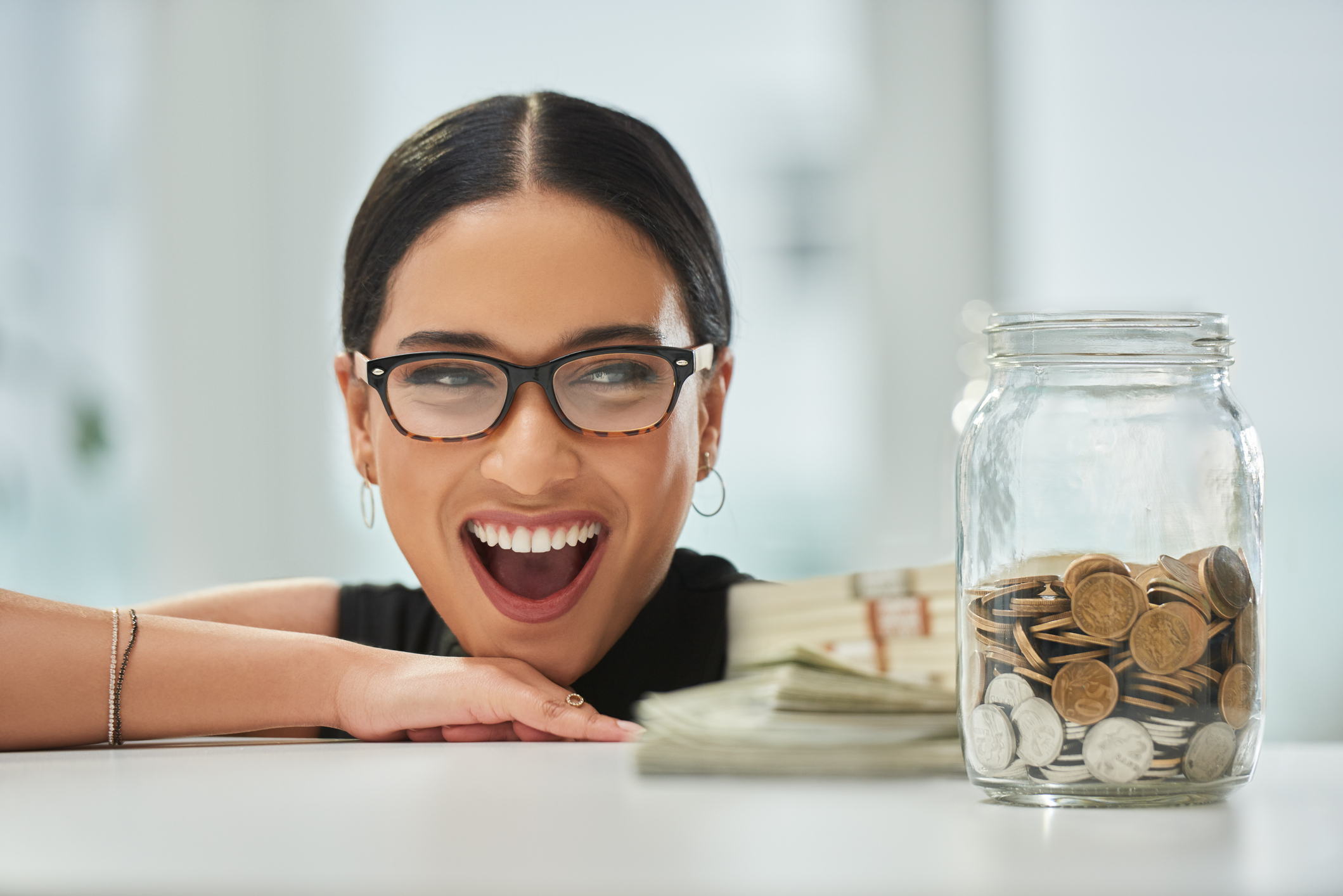 businesswoman looking excitedly over at a jar of coins and wads of cash in her office