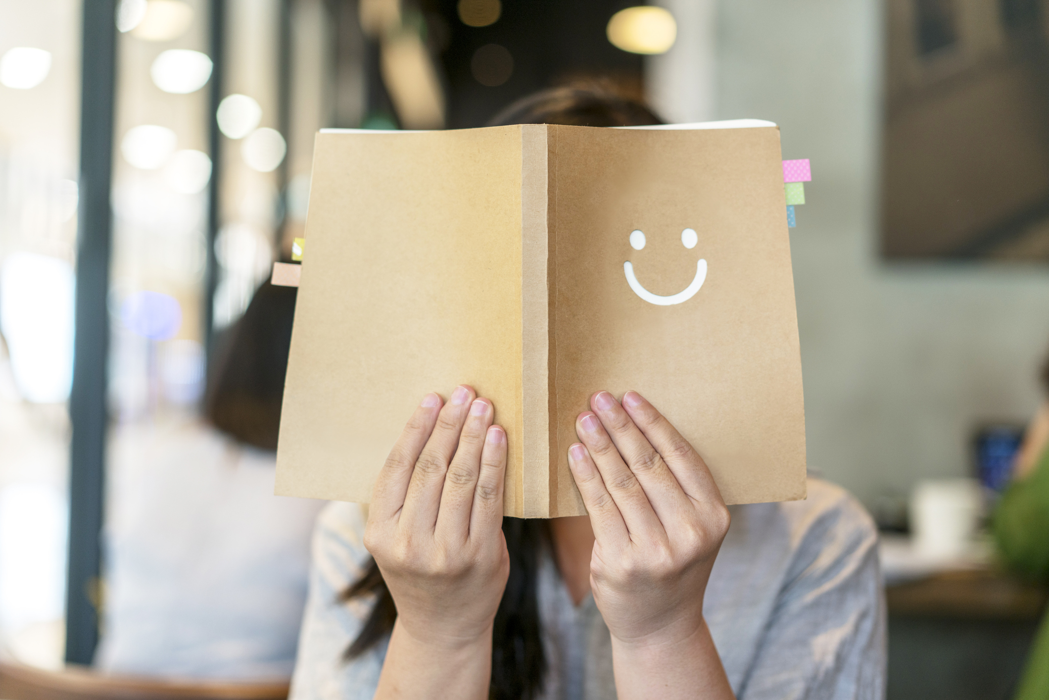 girl holding book covering face